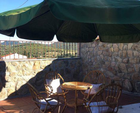 mesa y sillas de mimbre en solarium en Casa Juanin